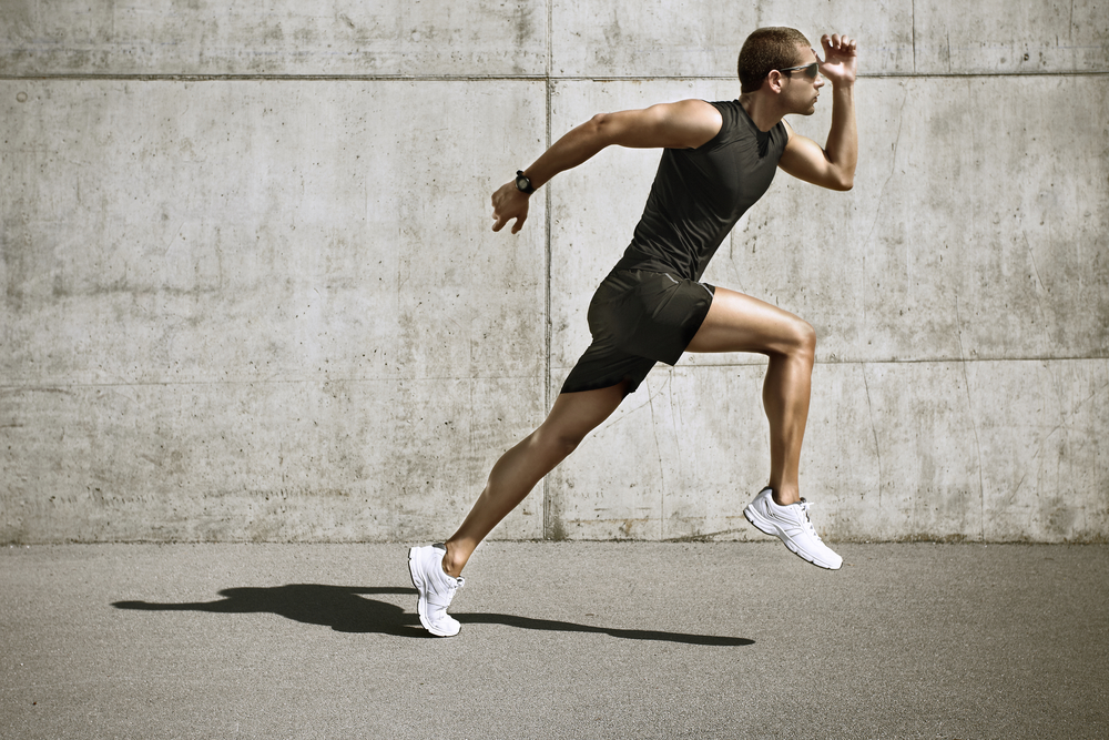 young man jogging front cement wall